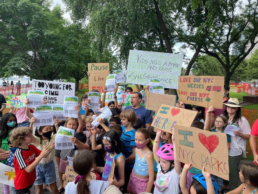 A photo of kids holding signs protesting the essential workers monument in Battery Park City