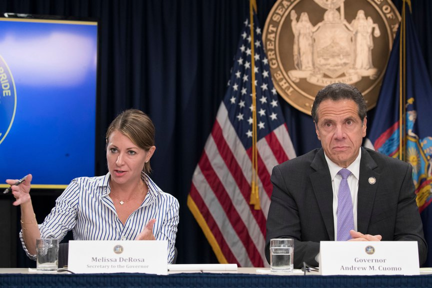 Melissa DeRosa answers questions while gesturing with her hands and with Governor Cuomo on her left, with the NY seal and flags behind them