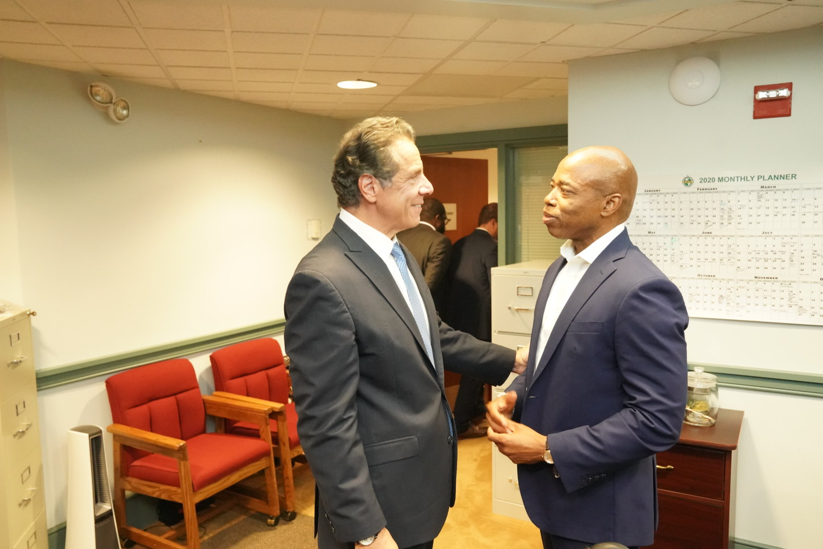 Governor Cuomo and Eric Adams smile at each other