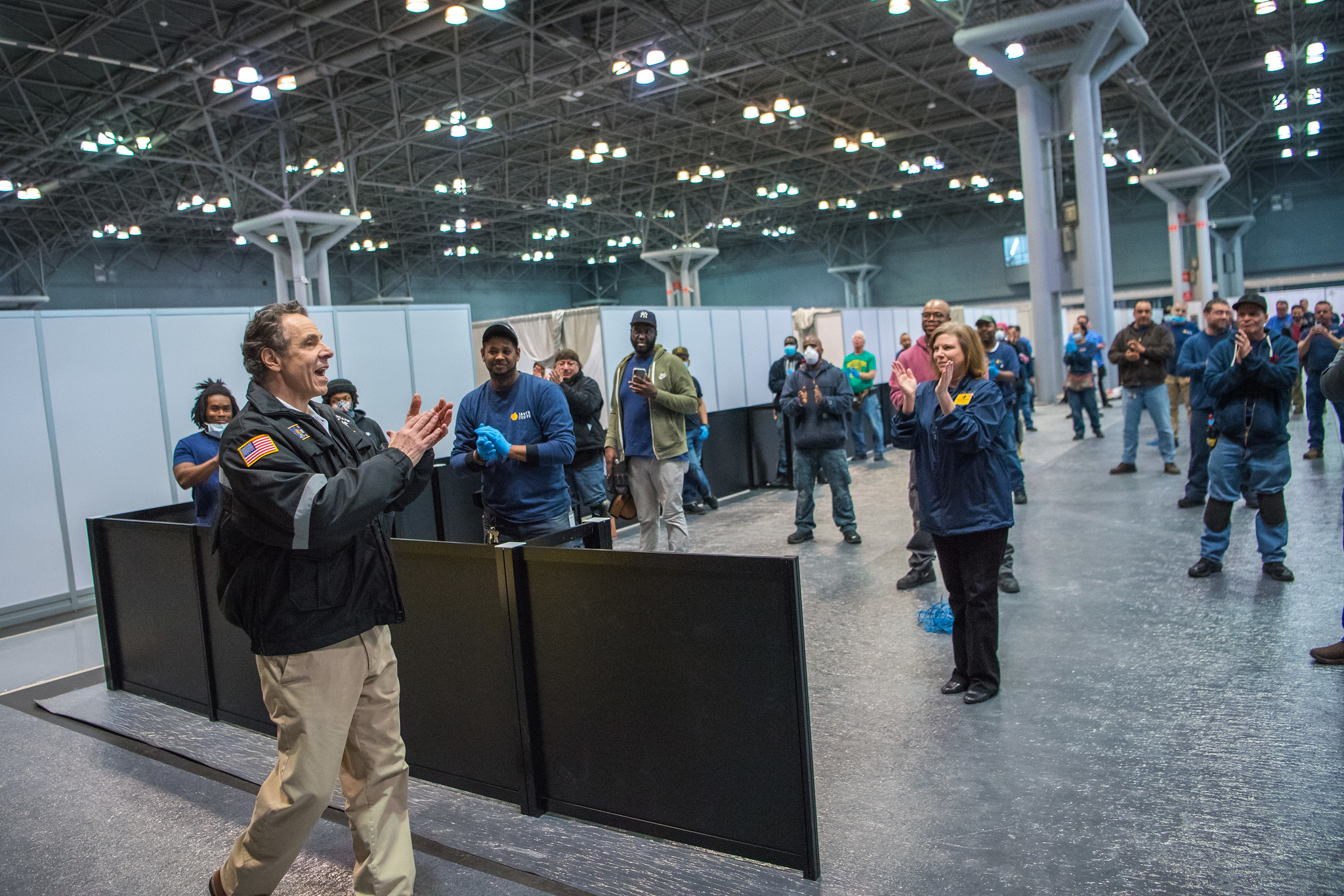 Governor Cuomo claps while walking through Javits Center where works have been setting up