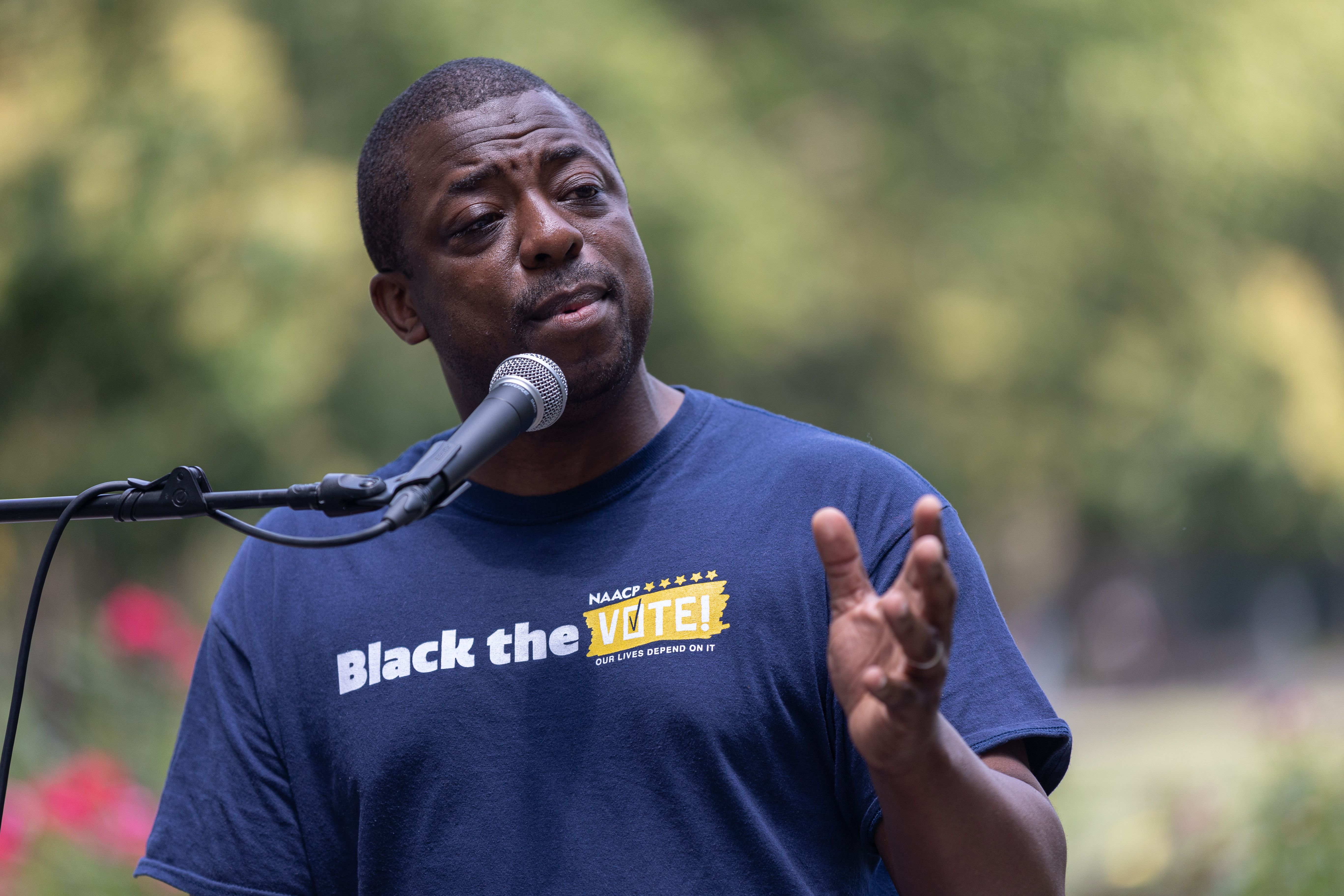 """Brian Benjamin at a lectern wearing a t-shirt that says """"Black the vote"""""""
