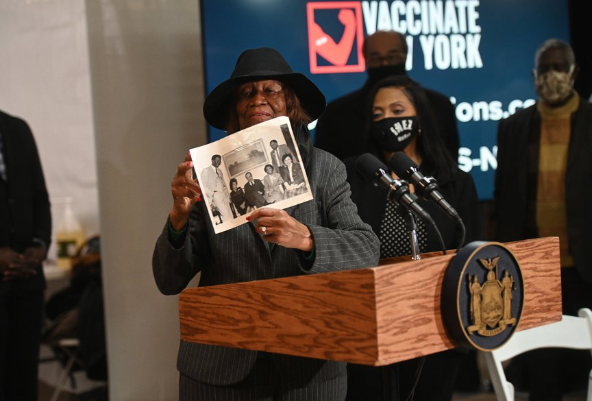 Hazel Dukes holds up a black and white photograph while standing next to a lectern