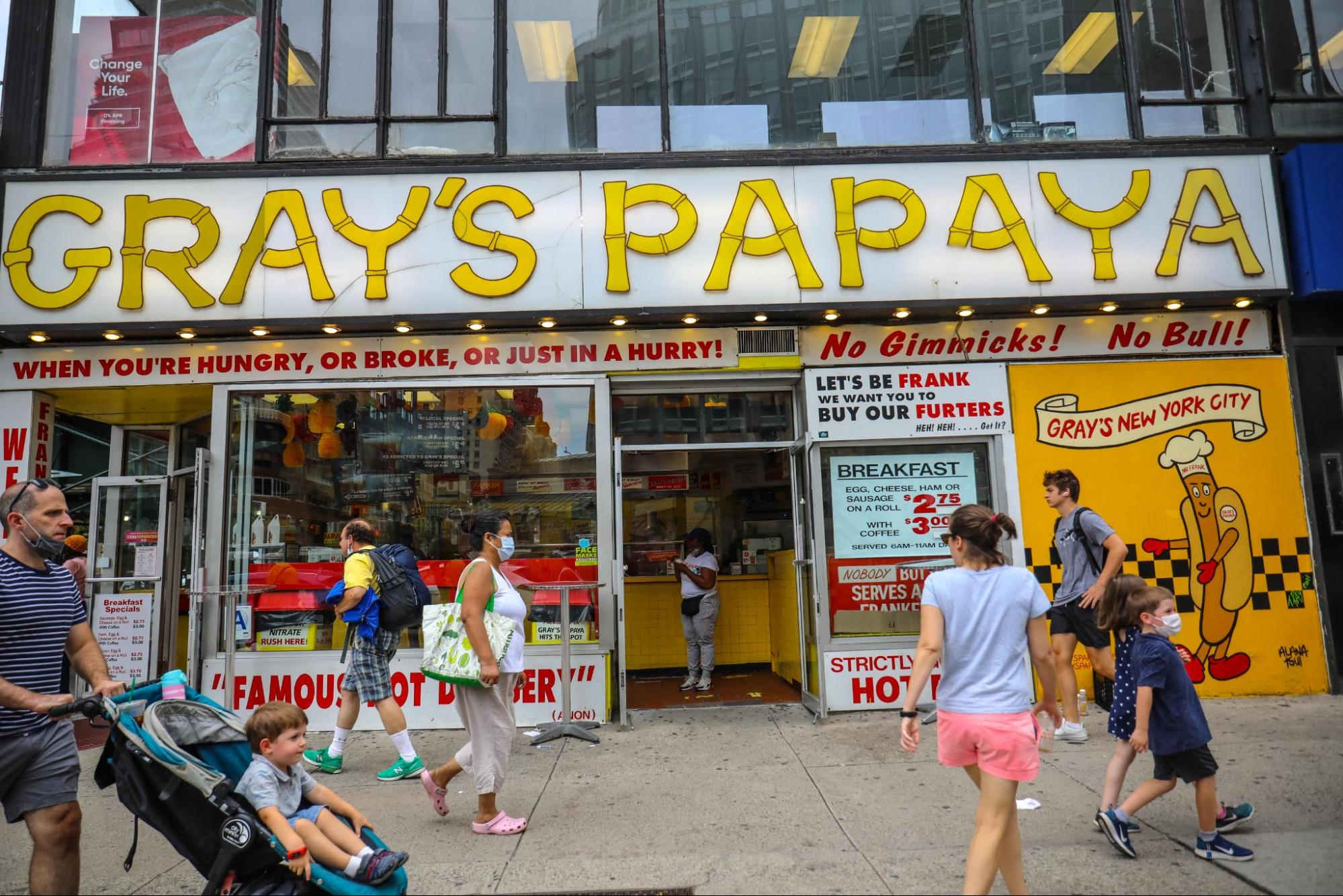 street view with pedestrians walking by gray's papaya