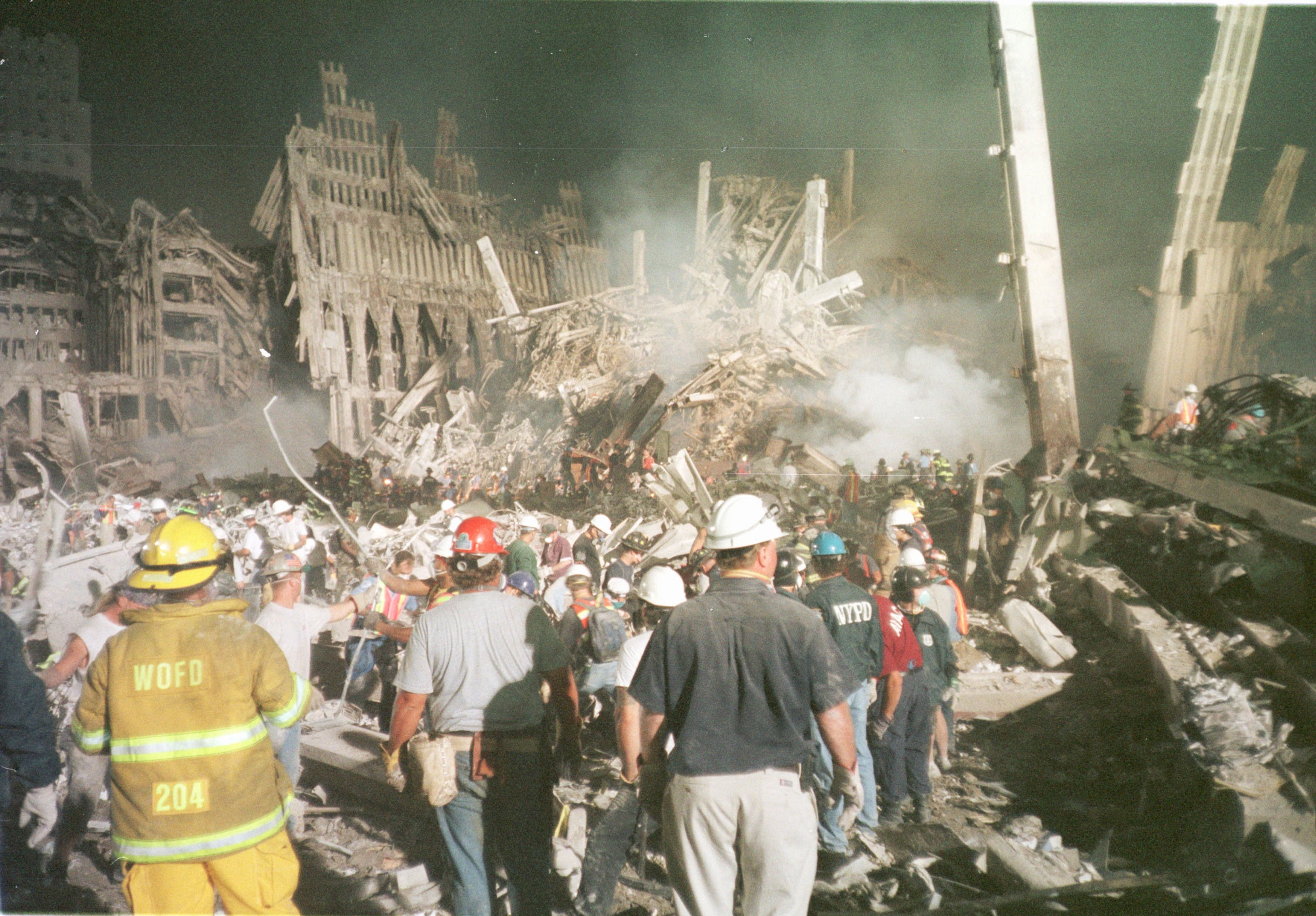 dozens of first responders stand in the dusty remains of the World Trade Center