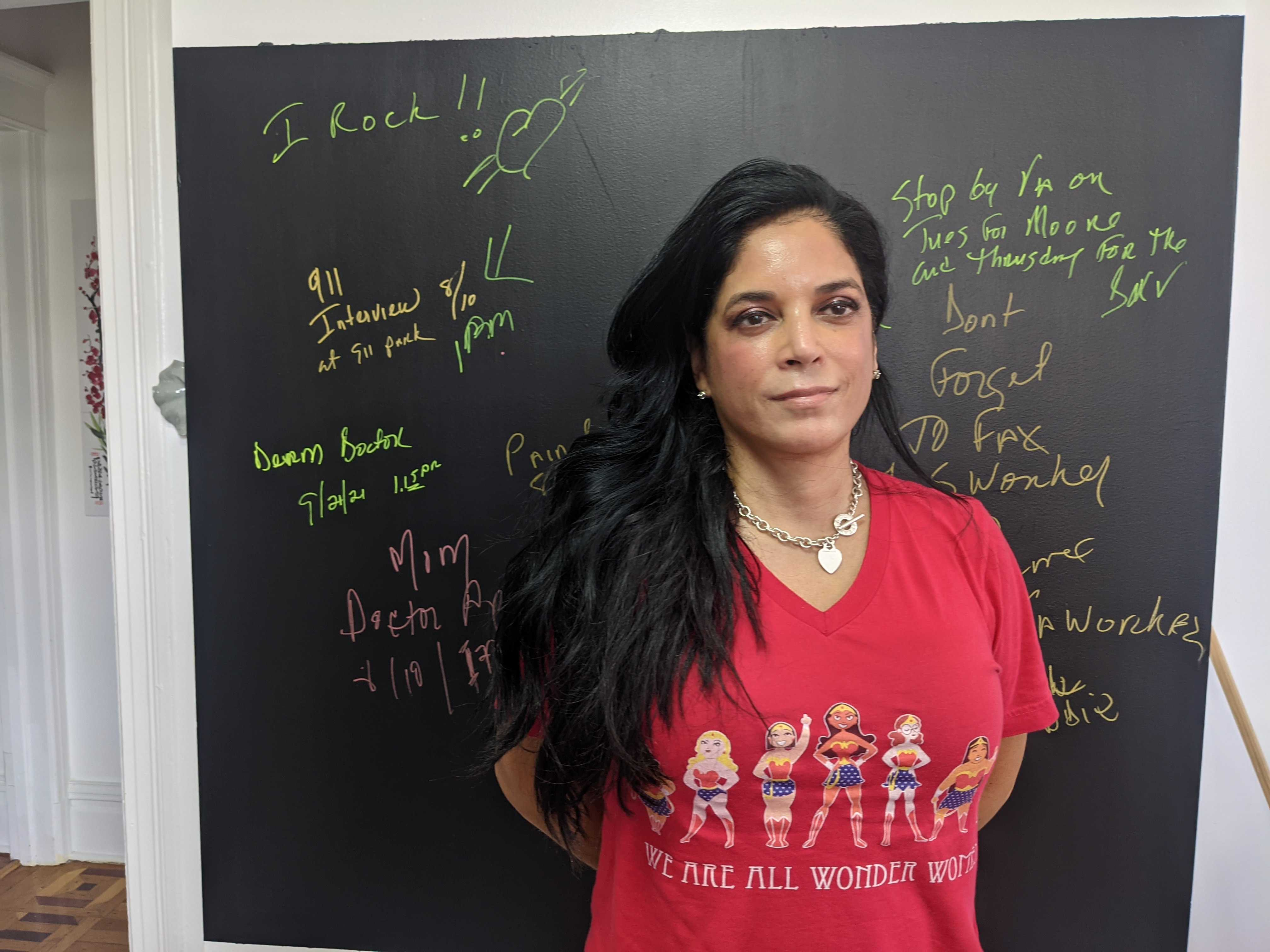 Ivonee Sanchez, in a red shirt, stands in front of a chalkboard
