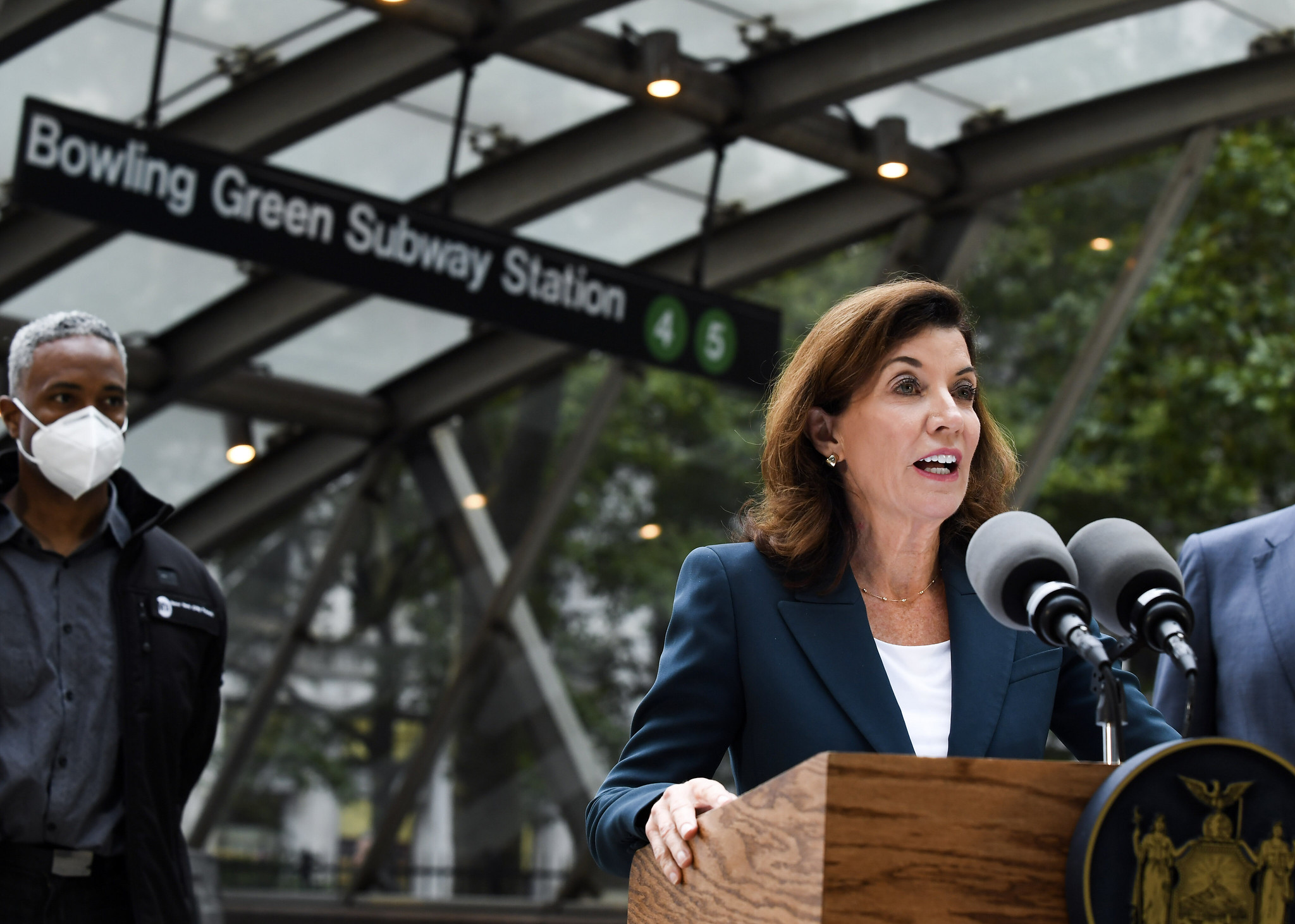 Governor Hochul, in a blue suit and white shirt, stands at a lectern outside the Bowling Greene Subway Station entrance