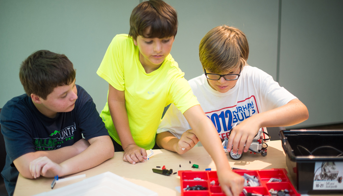 3 campers work on LEGOs