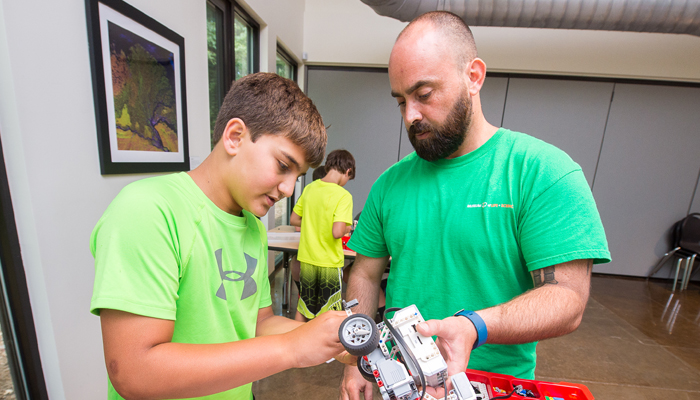 Camper and Counselor work on robot