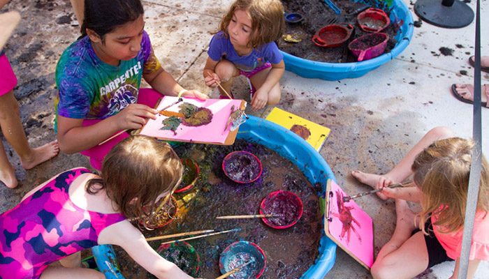 Campers doing art with colored mud