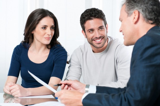 Consultant presents paperwork to a young couple.