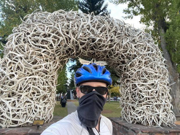 bicycling outfit with mask in front of elkhorn arch in Jackson Wyoming