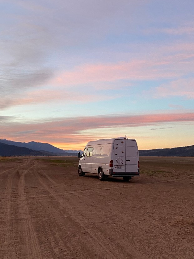 van on dry lakebed in sunset