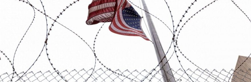 Flag waves over raiser wire fence.