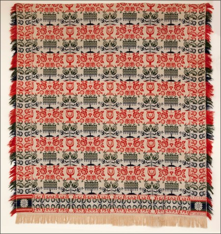blue, red, green and white woven coverlet in floral pattern