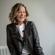 laughing woman, shoulder length hair, blond, black leather jacket