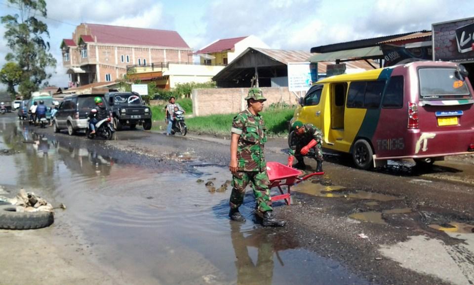 Foto: Solideo/Sumut Pos Danramil Tigapanah dan anggoatanya mengatur lalulintas, saat menimbun jalan yang rusak parah dengan batu, Senin (9/1) siang.