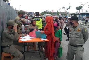 TERJARING RAZIA: Personel Satpol PP menindak warga yang tak mengenakan saat razia di Jalan Pelabuhan Raya depan kantor Pelindo 1 Belawan, Senin (14/9).