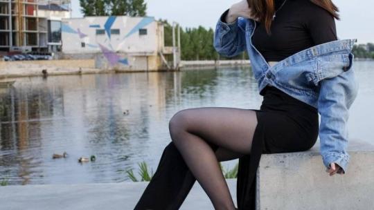 Девушка в черном платье и колготках