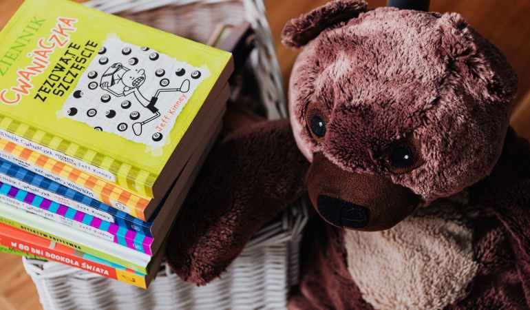 brown bear plush toy and stack of books