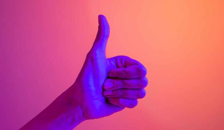 persons hand doing thumbs up