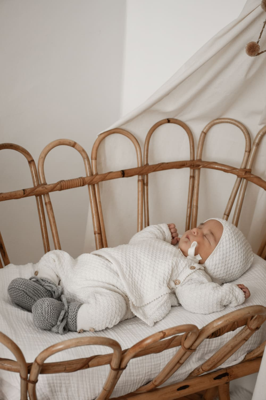 nouveau né dans un lit en rotin vintage