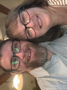 Ben Allison, left, wearing glasses and a striped button down shirt smiles at the camera with his arm around his mother Berneeta, also smiling at the camera in a striped t shirt and glasses