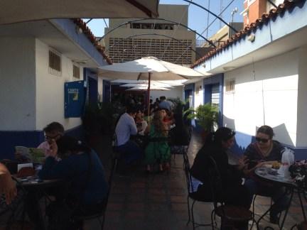 La terrasse du café, avec au dessus, la verrière cassée et les parasols installés pour l'occasion.