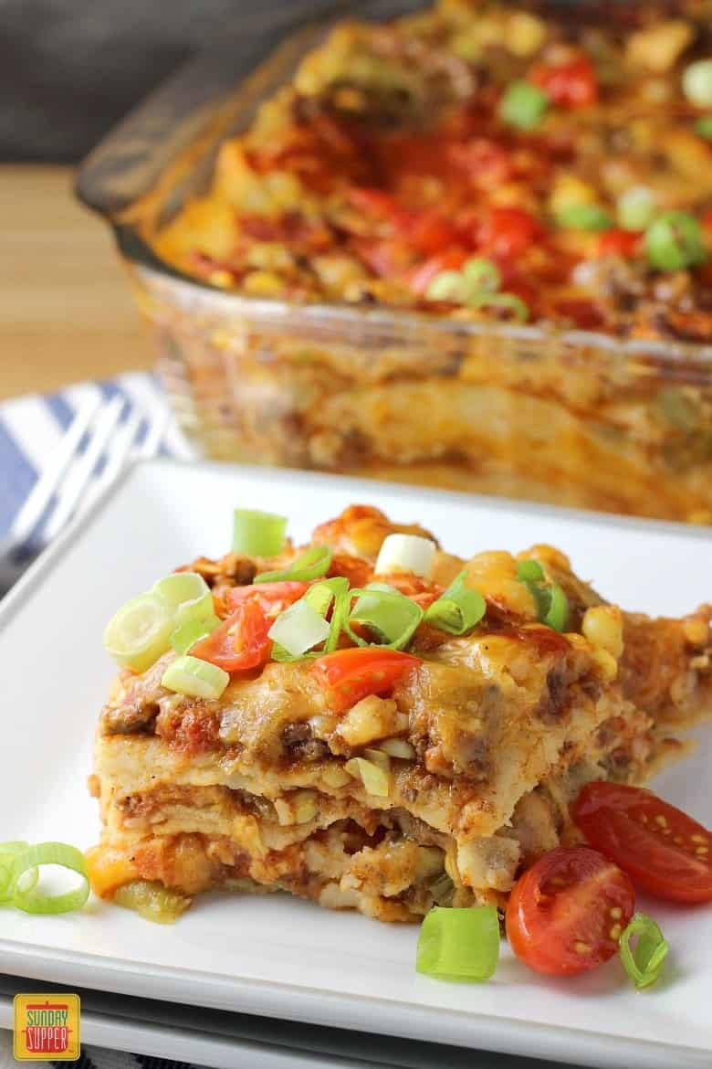 Mexican Lasagna with Corn Tortillas - a serving of Mexican lasagna on a white plate topped with green onions and tomatoes