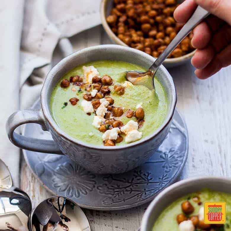 Easy Broccoli Soup with Spicy Roasted Chickpeas served with a spoon in a cup set on a saucer