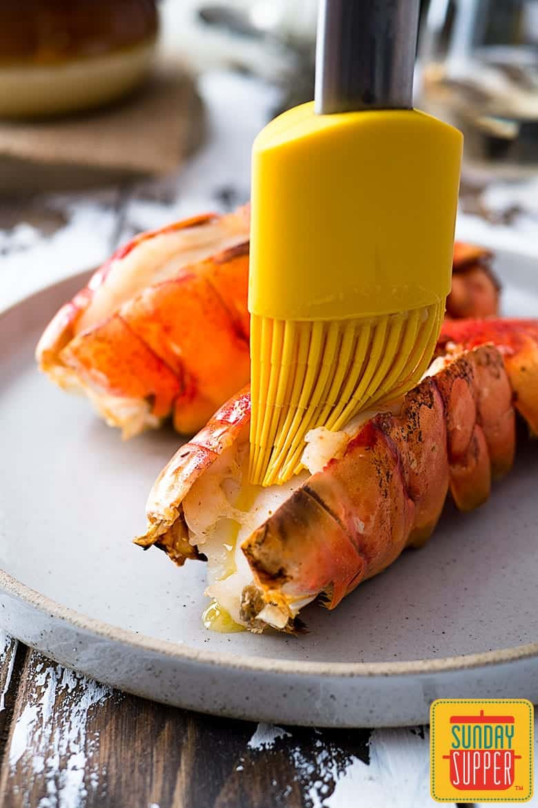 Slathering butter on lobster tails with cooking brush