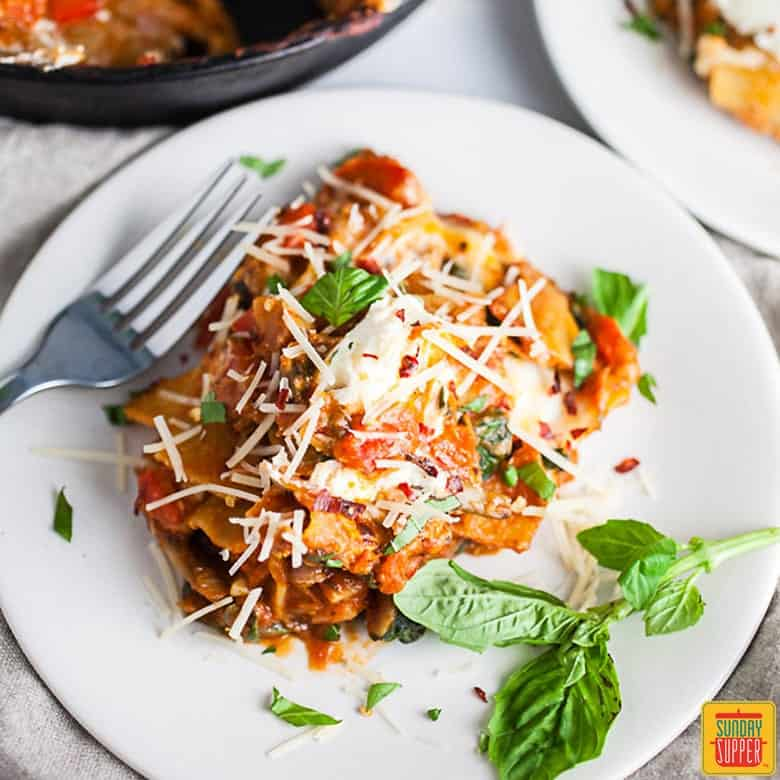 Cast Iron Skillet Lasagna on a white plate garnished with fresh basil leaves