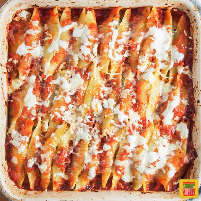 Pulled Pork Stuffed Shells in baking dish and topped with cheese