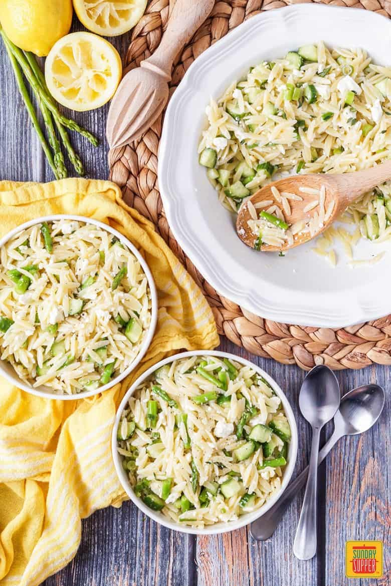 Lemon Orzo Pasta Salad in 2 serving bowls aside the serving platter with a wooden spoon and some juiced lemons