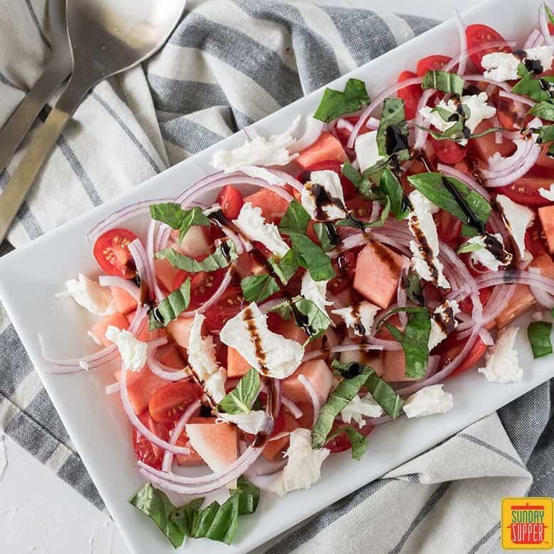 watermelon basil salad on white platter, on grey linen