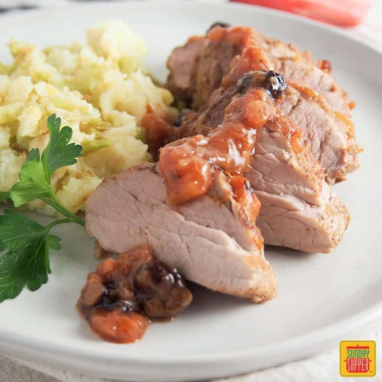 pork tenderloin with rhubarb chutney served with colcannon on a white plate