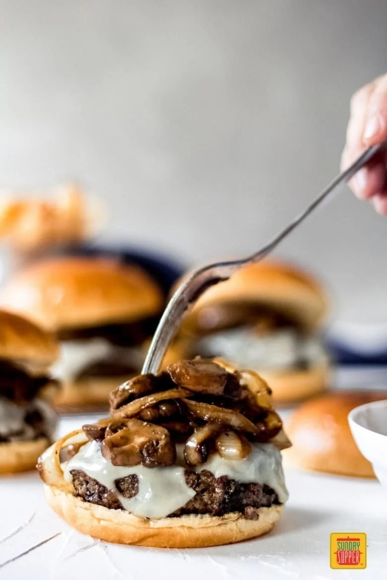 Placing sautéed mushrooms and onions on the Mushroom Swiss Burger with a fork