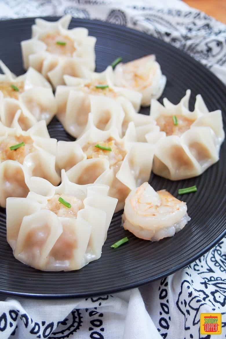 shrimp shumai served on a black plate topped with chives