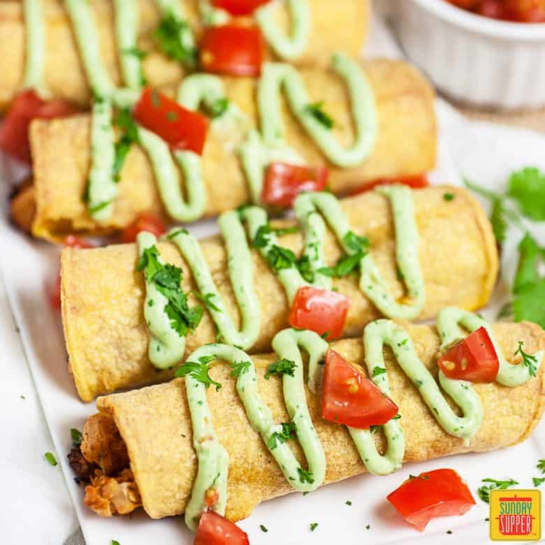 Chicken taquitos on a white surface with avocado crema drizzle