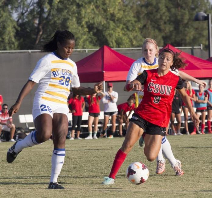 CSUN student (in red) keeps ball away from Riverside soccer player.