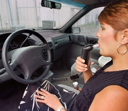 A woman using an ignition lock that signifies that she is sober enough to operate her vehicle.
