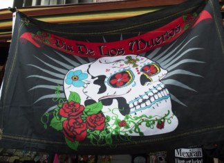 """A flag that advertises """"Dia de Los Muertos"""" (Day of the Dead). This holiday is celebraed on November 1 and November 2."""