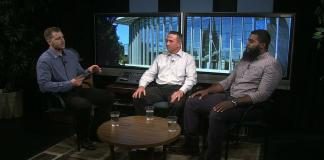 Three men sit along one another in interview