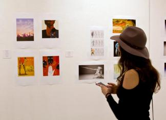 Woman looks at images hanging off wall