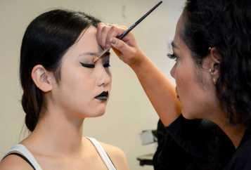 Makeup artist touches-up models eyeshadow before show