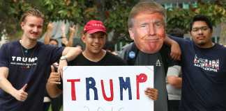 Trump supporters hold up trump 2016 poster while people in the background flip them off
