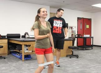 Photo shows intern instructing student with exercises