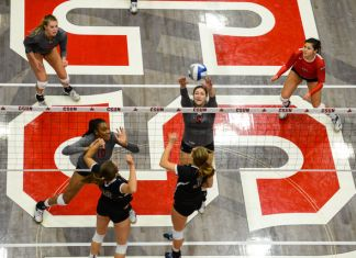 CSUN volleyball player hits the ball over the net