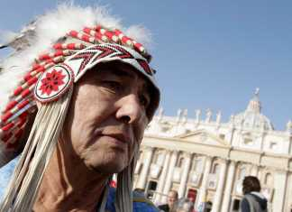 Photo shows native american woman wearing headress at St. Peters