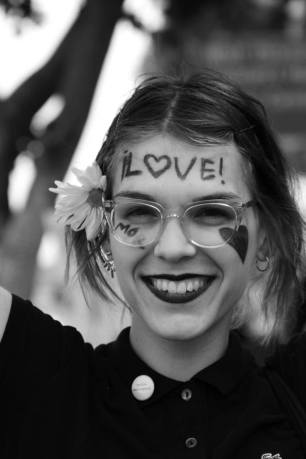 """Female protester is shown smiling with the word """"love"""" written across her forehead"""