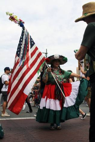Woman dressed in traditional Mexican attire with a long dress and large hat, holds up American flag